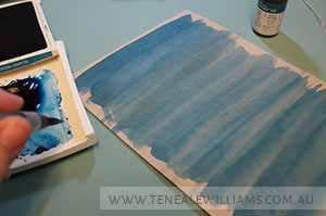 Creating a watercolor background by brushing Aqua Painter Crumb Cake cardstock with Island Indigo re-inker